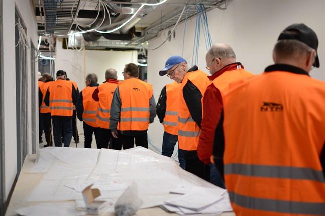Fredrik Herts (i blå keps) tittar intresserat på ritningarna till den nya kontorsdelen. Han skötte fastighetsservicen under de cirka sjutton år som han arbetade på NTM.