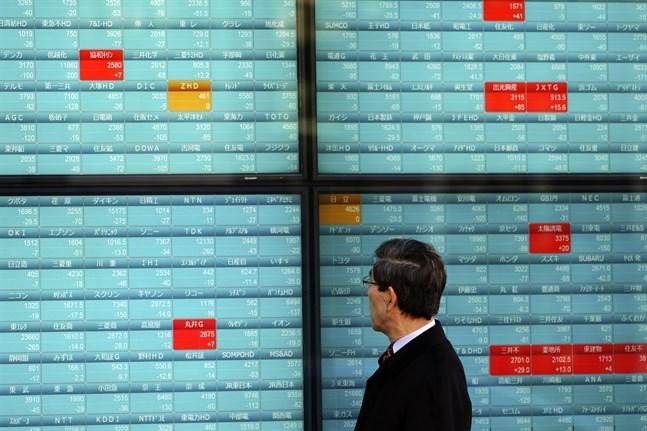 En man går förbi en elektronisk tavla där Nikkeis kurser rapporteras. Bild från måndagen.