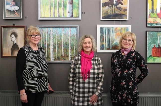 """Mellan Lisa Lillqvist (längst till vänster i bild) och Maj-Britt Smedjebacka syns Denice Björks målning """"Höst"""", som är målad med palettkniv. Längst till höger står Gurli Rönnqvist. Alla har de med arbeten i Larsmo konstklubbs årsutställning."""