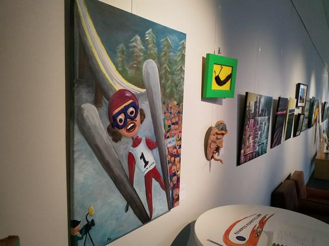 """Titta, jag flyger heter den här tavlan i akryl av Patrick """"Pö"""" Östman, ett av omkring 70 konstverk som Närpes konstklubbs medlemmar ställer ut i konsthallen. Bredvid tavlan Överlevaren i akryl av Östman, under Glad viking av Jonna Nykänen."""
