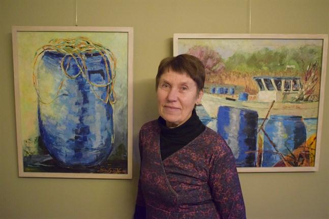 Solvej Fågelbärj-Hannula ställer bland annat ut oljemålningarna Plasttunna i sol och Vår i fiskehamnen, båda från 2006.