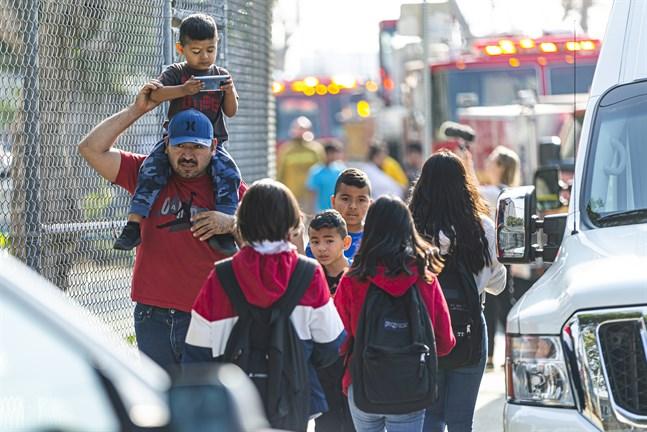 Barn evakueras efter att de och deras skola i stadsdelen Cudahy i Los Angeles fått flygbränsle släppt på sig.