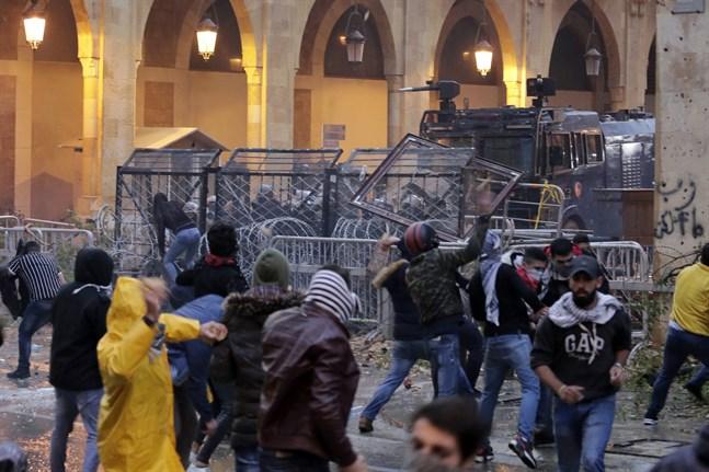 Demonstranter drabbar samman med kravallpolis vid en av vägarna som leder fram till Libanons parlament i Beirut.