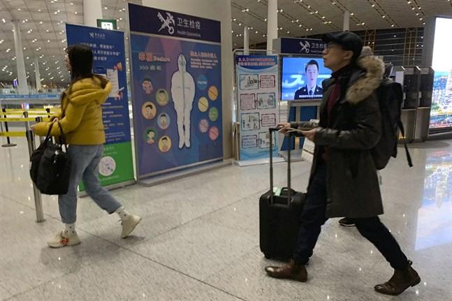 Resenärer passerar en hälsokontroll vid den internationella flygplatsen i Peking. Bilden togs den 13 januari.