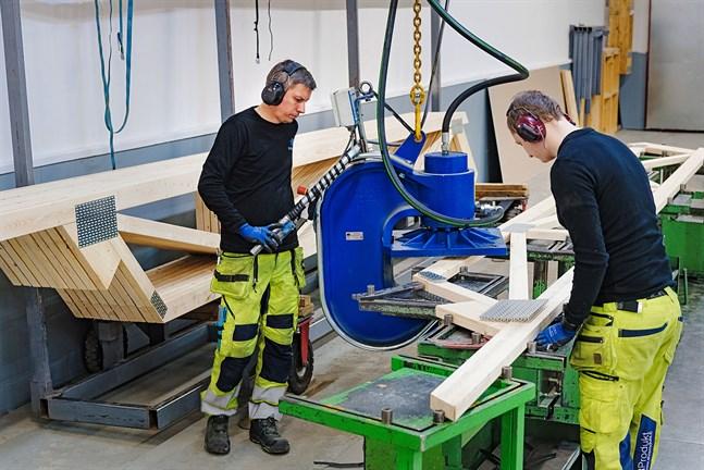 Krister Östman och Ronnie Asplund jobbar med att konstuera takstolar. Spikplåtarna fästs i trät med en fyrtio tons press.