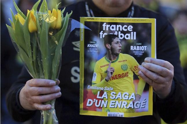 En Nantes-supporter med en fotbollstidning vars omslag pryds av Emilano Sala. Arkivbild.