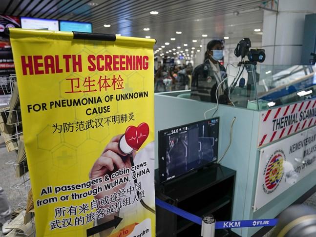 Personal på Malaysias flygplats i Kuala Lumpur hälsokollar alla passagerare.
