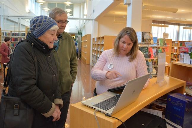 Astrid och Bengt Jossfolk bekantar sig med bibliotekets  digitala utbud. Sofia Österberg guidar dem.