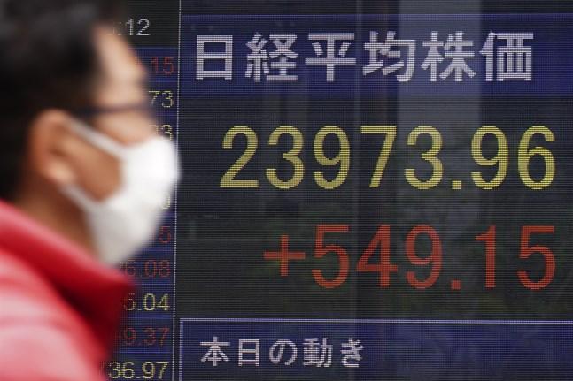 En man går förbi en skärm som visar Japans Nikkei225-index.
