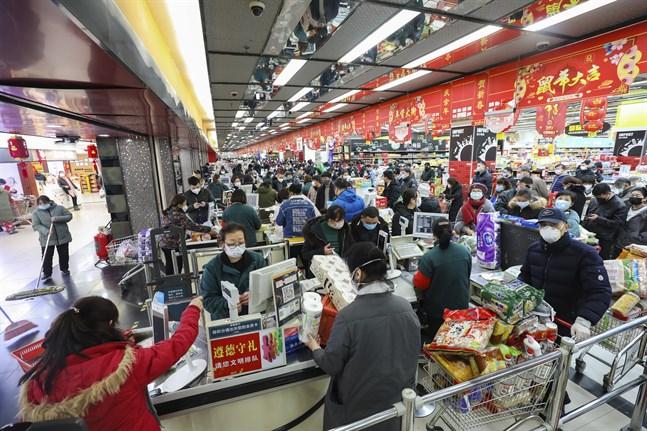 Invånare i Wuhan handlar mat med ansiktsmasker på.