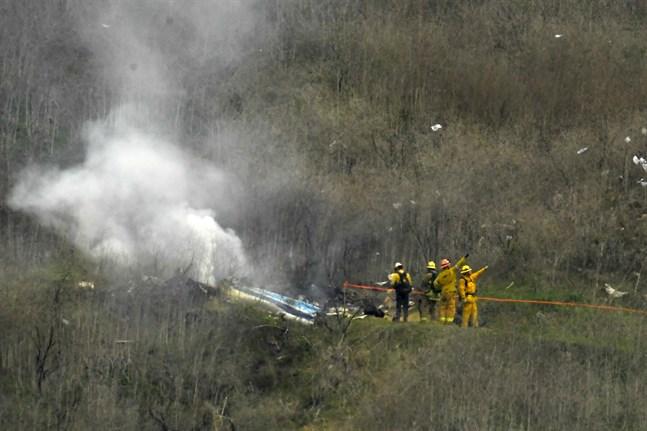 Brandmän jobbar vid platsen där Kobe Bryants helikopter kraschade.