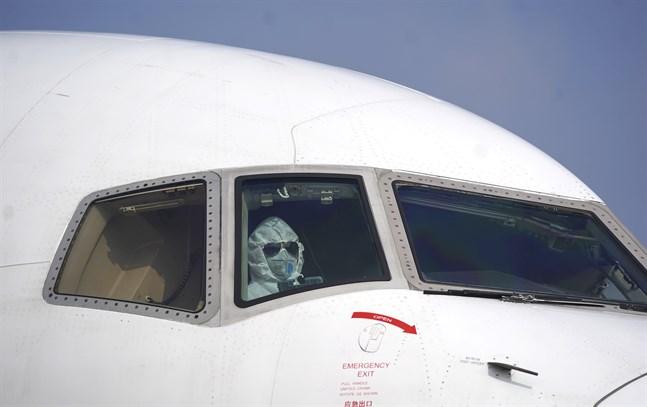 En pilot i skyddsutrustning i ett flygplan på flygplatsen i Wuhan.