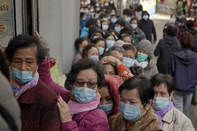 Människor köar för att köpa munskydd vid en butik i Hongkong.