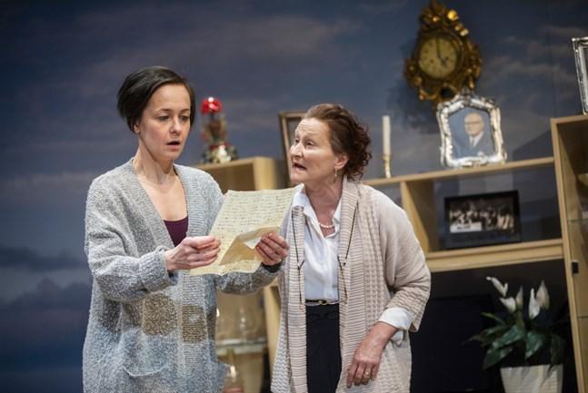 Maija (Anna Lemmetti Vieri), till höger, har berättat för sin dotter Kata (Emmi Kangas) att det är fullt möjligt att Urho Kekkonen är hennes riktiga far. Maija visar bland annat ett brev som Kekkonen skrivit till henne.