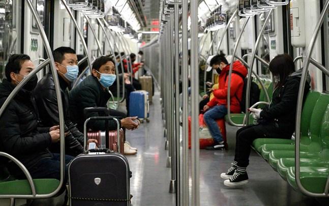 Resenärer använder ansiktsmasker på metron i Shanghai.