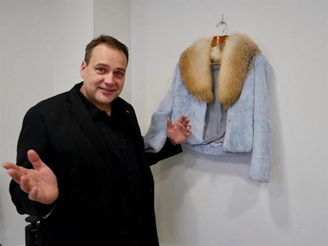 """Steven Frostdahl, informationschef för Fifur i Österbotten, visar upp en päls som gjorts av designstuderande vid Novia för serien """"Alice in furland""""."""