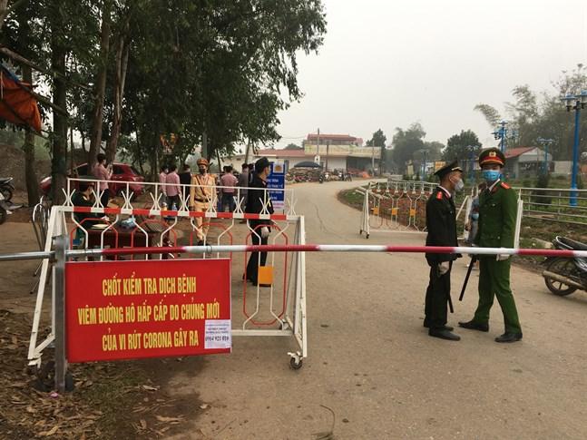Poliser på vakt vid en vägspärr vid Son Loi utanför Vietnams huvudstad Hanoi under torsdagen. Området är försatt i karantän sedan sex fall av coronaviruset covid-19 upptäckts där.
