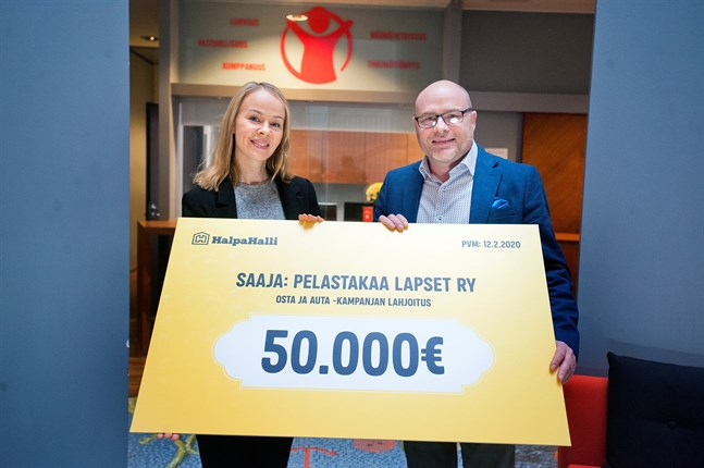 Heli Le tar emot donationen till Rädda Barnen från Halpa-Hallis marknadschef Juha Hakala.