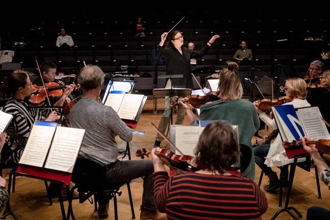 Anna-Maria Helsing dirigerar MÖK under torsdagens repetition i konservatoriets sal.