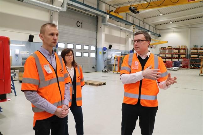 Projektledare Matias Nygård, marknadsföringschef Ullamay Borgmästars och vice vd Andreas Björk i produktionshallen där också truckarna testas innan leverans.