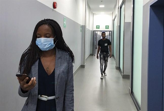 En kvinna i ett köpcentrum i Zambia försöker skydda sig mot virusspridning. Arkivbild.