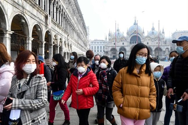 Turister i Venedig bär munskydd då de besöker Piazza San Marco. Över 1 000 personer har smittats av coronaviruset i Italien.
