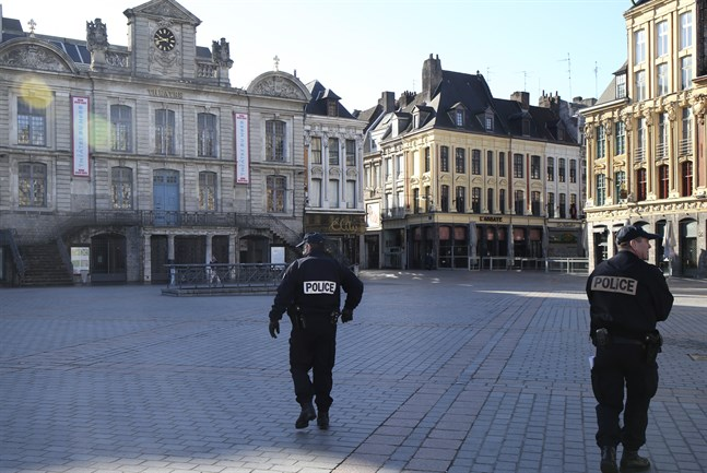 Polis patrullerar ett tomt torg i Lille i norra Frankrike.