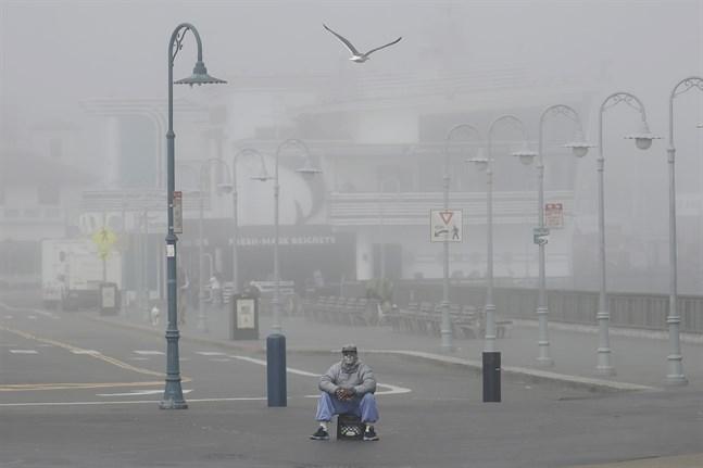 En gatuartist sitter ensam i Fisherman's Wharf i San Francisco på torsdagen. Även Kaliforniens invånare beordras att stanna hemma.