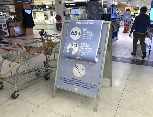 Skyltar i en belgisk matvarubutik manar till minst en meters avstånd mellan kunderna - och ger pensionärer och vårdanställda rätt att gå före i kön.