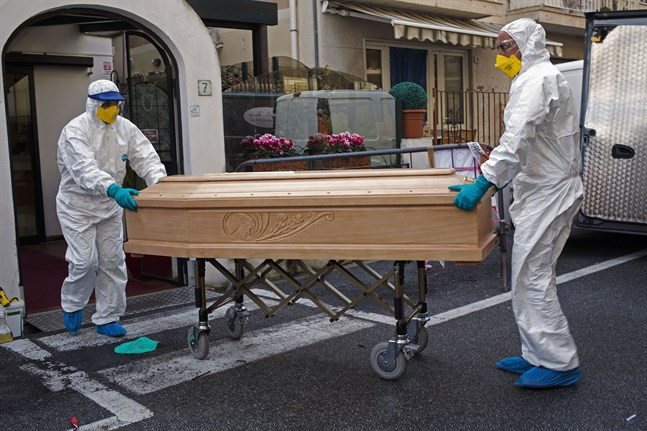 En avliden kvinna bärs ut från hotellrummet i Laigueglia i norra Italien där hon avled i covid-19. Bilden är från tidigare i mars. Arkivbild.