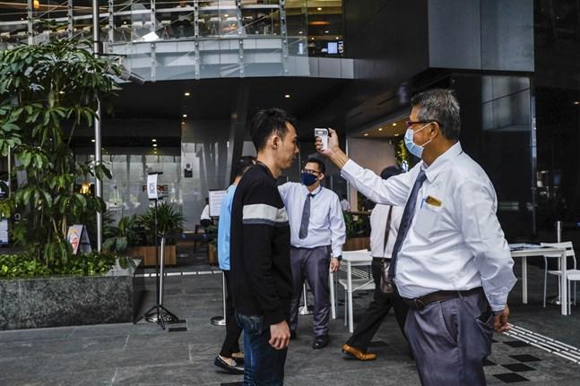 En man febertestas innan han ska gå in i en kontorsbyggnad i Singapore. Arkivbild.