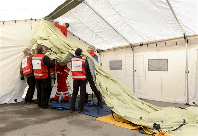 Finlands Röda Kors frivilliga reser en triage-enhet utanför Hyvinge sjukhus.