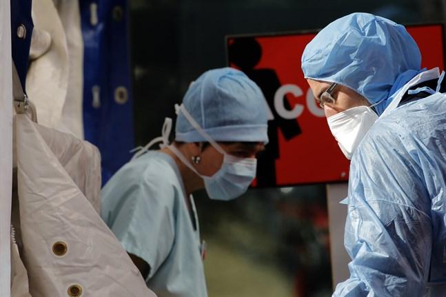 Läkare utanför ett tält som används som ett väntrum för personer med coronasymtom vid ett Parissjukhus.
