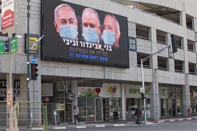 Israels premiärminister Benjamin Netanyahu isolerar sig efter att möjligen ha kommit i kontakt med en smittad medarbetare vid ett knesset-sammanträde. Skylten på bilden sitter i Tel Aviv och visar Netanyahu och ledarna för de två främsta oppositionspartierna, Benny Gantz och Avigdor Lieberman.