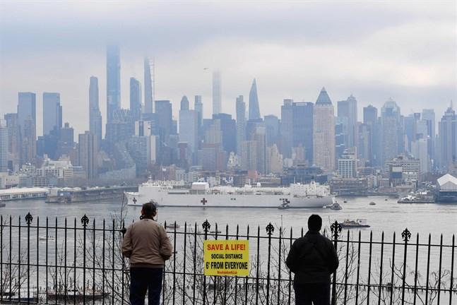 Två personer ser på när fartyget USNS Comfort anländer längs Hudsonfloden i New York på måndagen.