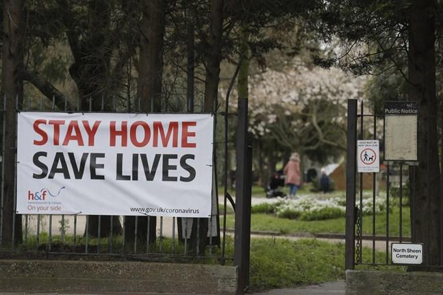 En stor skylt med ett tydligt budskap – stanna hemma, rädda liv – vid en park i London.