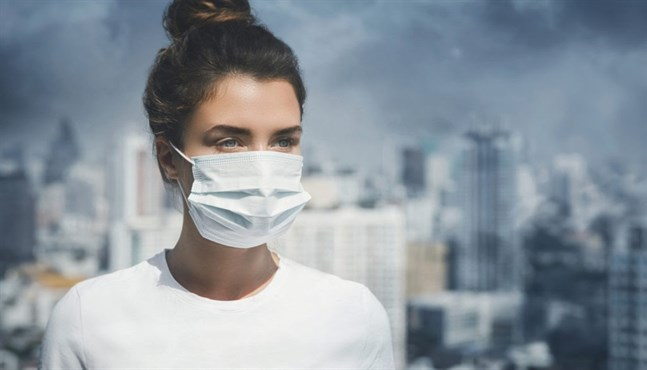 Woman wearing face mask because of air pollution in the city