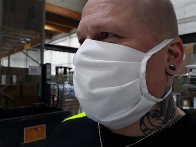 Tom Helin testar en ansiktsmask av tyg som vårdarna inom öppenvården ska använda. De ska tvättas i 90 grader efter några timmars användning.
