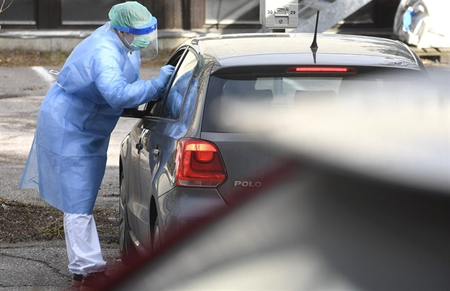 A sampler takes samples in protective clothing at a testing drive-in station on Wednesday, 18th March, 2020 in Espoo, Finland. The station is aimed to the health and hospital professionals.