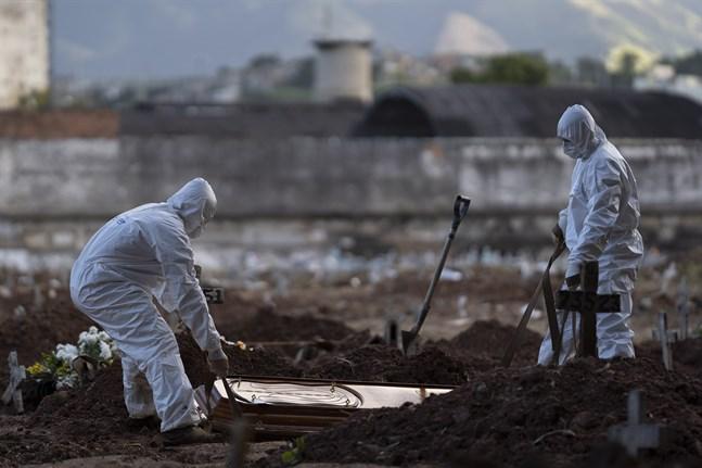 Kyrkogårdsarbetare begraver en avliden i Rio de Janeiro.