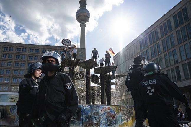 En brokig skara demonstranter protesterar mot coronarestriktioner uppe i en fontän på Alexanderplatz i Berlin.