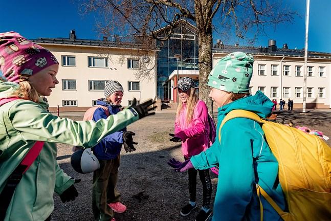Andraklassisterna Ellen Marttila, Minea Kupari, Venla Kurtén och Hilda Leipälä leker sten-sax-påse på gården innan nystarten i Villa skola.