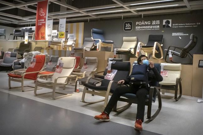 En man med munskydd provar en stol på Ikea i Peking. Arkivbild.