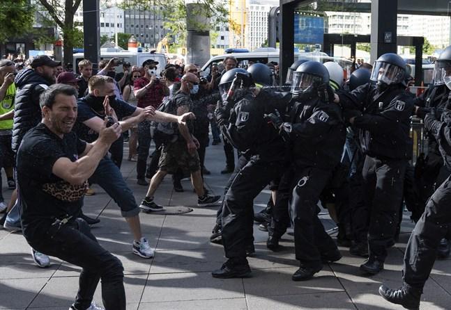 Polis använder sig av pepparsprej för att skingra demonstranter vid Alexanderplatz i Berlin den 9 maj.