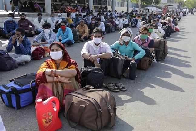 Migrantarbetare från andra delstater väntade på söndagen på en järnvägsstation i Ahmedabad i Indien. Tiotusentals migrantarbetare har mist arbetet på grund av nedstängningen i landet.