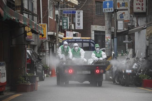 Personer i skyddsmundering sprejar desinficeringsmedel på en gata i Seoul i Sydkorea tidigare i veckan. Metoden får tummen ner av WHO.