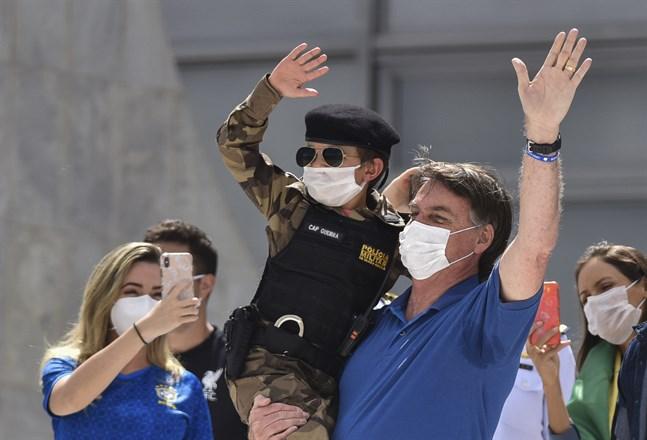 Brasiliens president Jair Bolsonaro med ett barn klädd i militärpolisuniform under en demonstration i Brasilia i söndags till stöd för presidentens krav på att avveckla coronarestriktioner och öppna upp ekonomin.