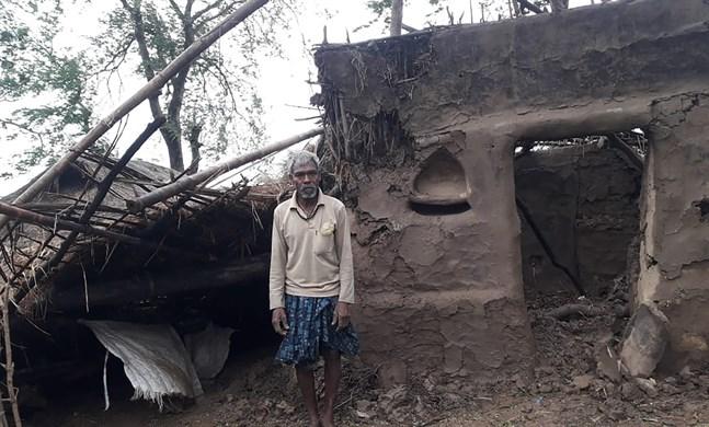 En bybo framför sitt hus som skadats av cyklonen Amphans framfart i distriktet Bhadrak i delstaten Odisha i Indien.