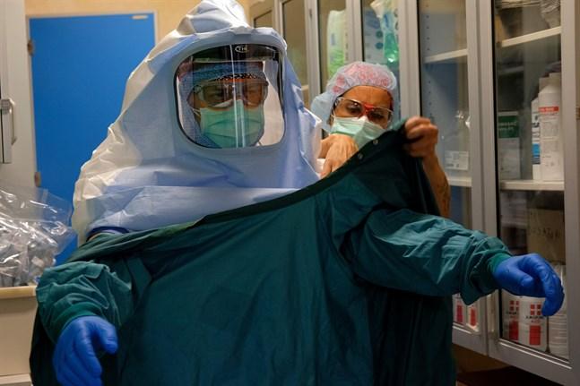 En sjuksköterska hjälper en kollega att sätta på sig skyddsutrustning vid en covid-19-avdelning i Rom i mitten av april.