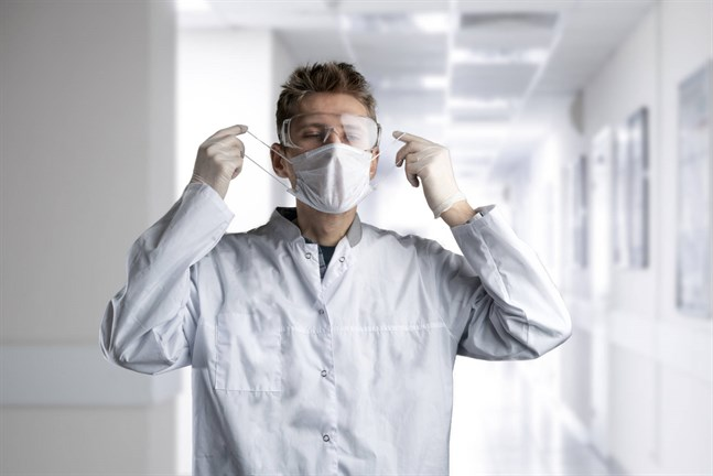 A doctor put on protective uniform with mask and eye glasses in the hospital.